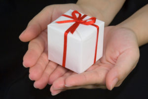Hands holding a gift with a black background